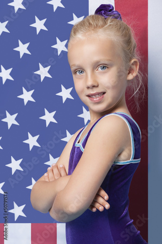 Portrait of a happy young female gymnast with arms crossed standing in front of American flag