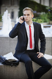 Young businessman sitting on platform while using cell phone