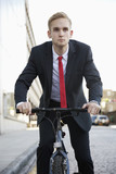Young businessman riding bicycle on street