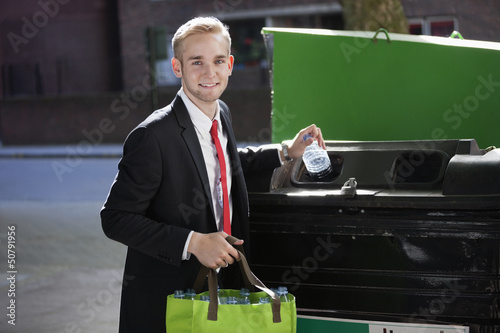 Portrait of young businessman throwing plastic bottles in bin