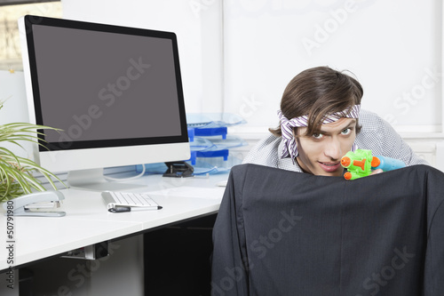 Portrait of young businessman aiming with toy gun at desk