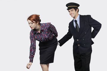 Portrait of young pilot touching flight attendant inappropriately against gray background