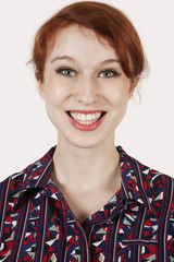 Portrait of happy young woman in shirt against gray background