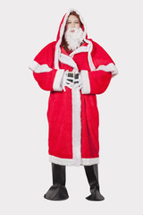 Portrait of young woman in Santa costume standing against gray background