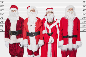 People in Santa costume standing side by side against police lineup