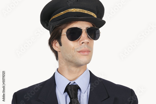 Close-up of young male pilot in uniform against white background