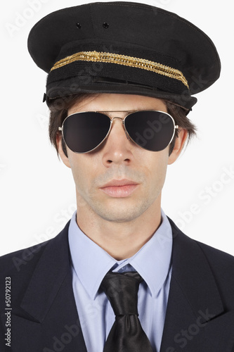 Close-up of young man in pilot uniform against white background