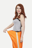 Portrait of young Caucasian woman oversized orange pants against gray background