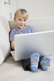 Portrait of happy young boy using laptop on sofa
