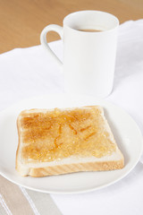 Jam on slice of bread with cup of coffee