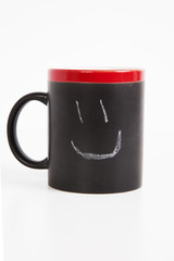 Close-up of smiley drawn on cup over white background