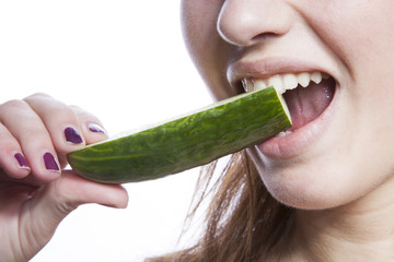 Detail shot of woman eating cucumber over white background
