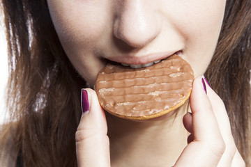 Detail shot of young woman eating cookie
