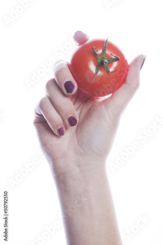 Detail shot of woman holding tomato over white background