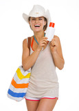Smiling young beach woman in hat holding sun screen creme