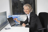 Portrait of senior businesswoman examining laptop with the use of stethoscope at office desk