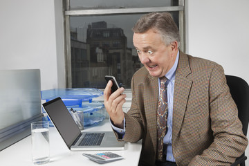 Angry middle-aged businessman looking at cell phone in office