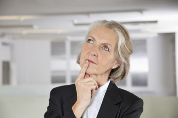 Thoughtful senior businesswoman looking up in office