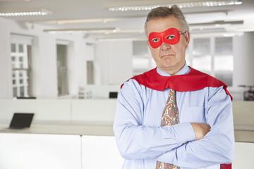 Portrait of serious businessman in superhero costume in office