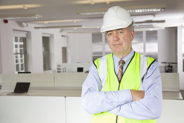 Portrait of middle-aged man in reflector vest and hard hat at office