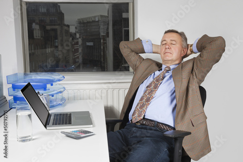 Middle-aged businessman resting on chair in front of laptop in office