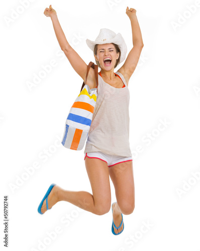 Smiling young beach woman in hat jumping