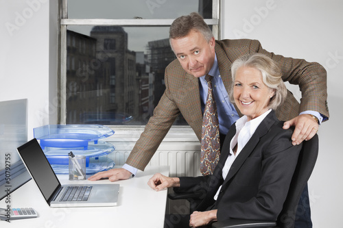 Portrait of businesswoman and man with laptop at desk in office