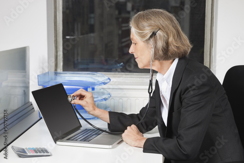 Side view of senior businesswoman examining laptop with the use of stethoscope at office desk