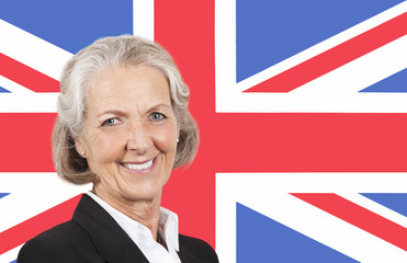 Portrait of smiling senior businesswoman over British flag