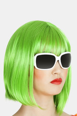 Young woman wearing green wig over gray background