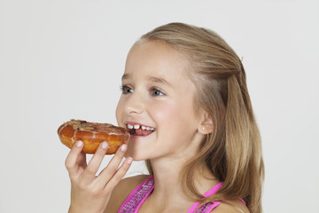 Portrait of young girl eating donut against gray background