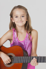 Portrait of young girl playing guitar against gray background