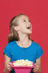 Portrait of surprised young girl holding popcorn container against red background