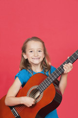 Portrait of girl playing guitar against red background