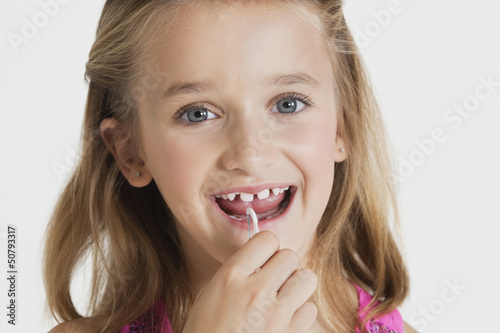 Portrait of young girl flossing teeth against gray background