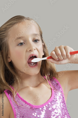 Young girl brushing teeth against gray background