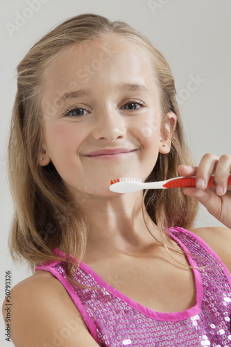Portrait of young girl holding toothbrush against gray background