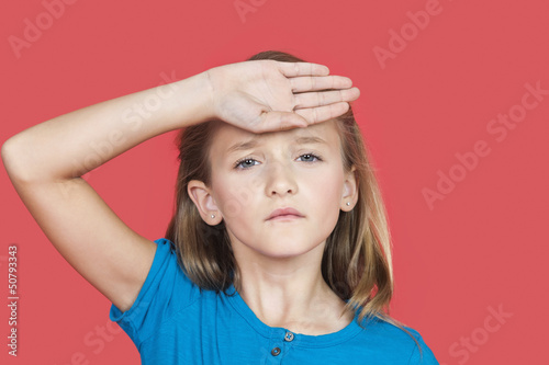 Portrait of young girl checking self temperature against red background