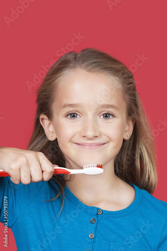 Portrait of girl holding toothbrush against red background