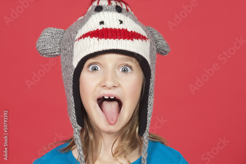 Portrait of girl sticking out tongue against red background