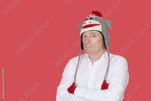 Portrait of confused senior man with arms crossed against red background