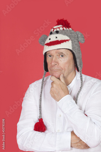 Portrait of thoughtful senior man with hand on chin against red background