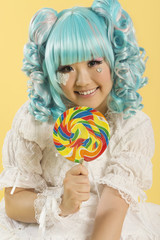 Portrait of smiling young woman dressed as a doll holding lollipop over yellow background