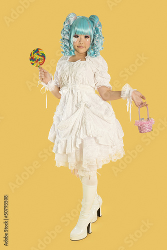 Full length portrait of young woman dressed as a doll holding lollipop over yellow background