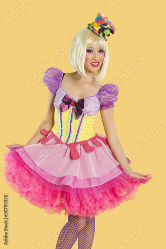 Portrait of young woman in doll's costume posing against yellow background