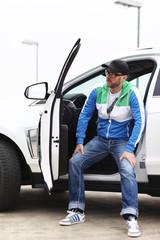 männliches Model sitzt weißem Auto