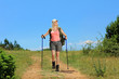 A young woman with backpack and hiking poles walking