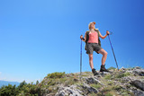 A young  woman with backpack and hiking poles posing