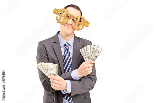 A young man wearing dollar sign glasses and holding US dollars
