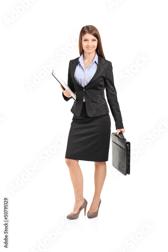 Full length portrait of a businesswoman with clipboard holding a